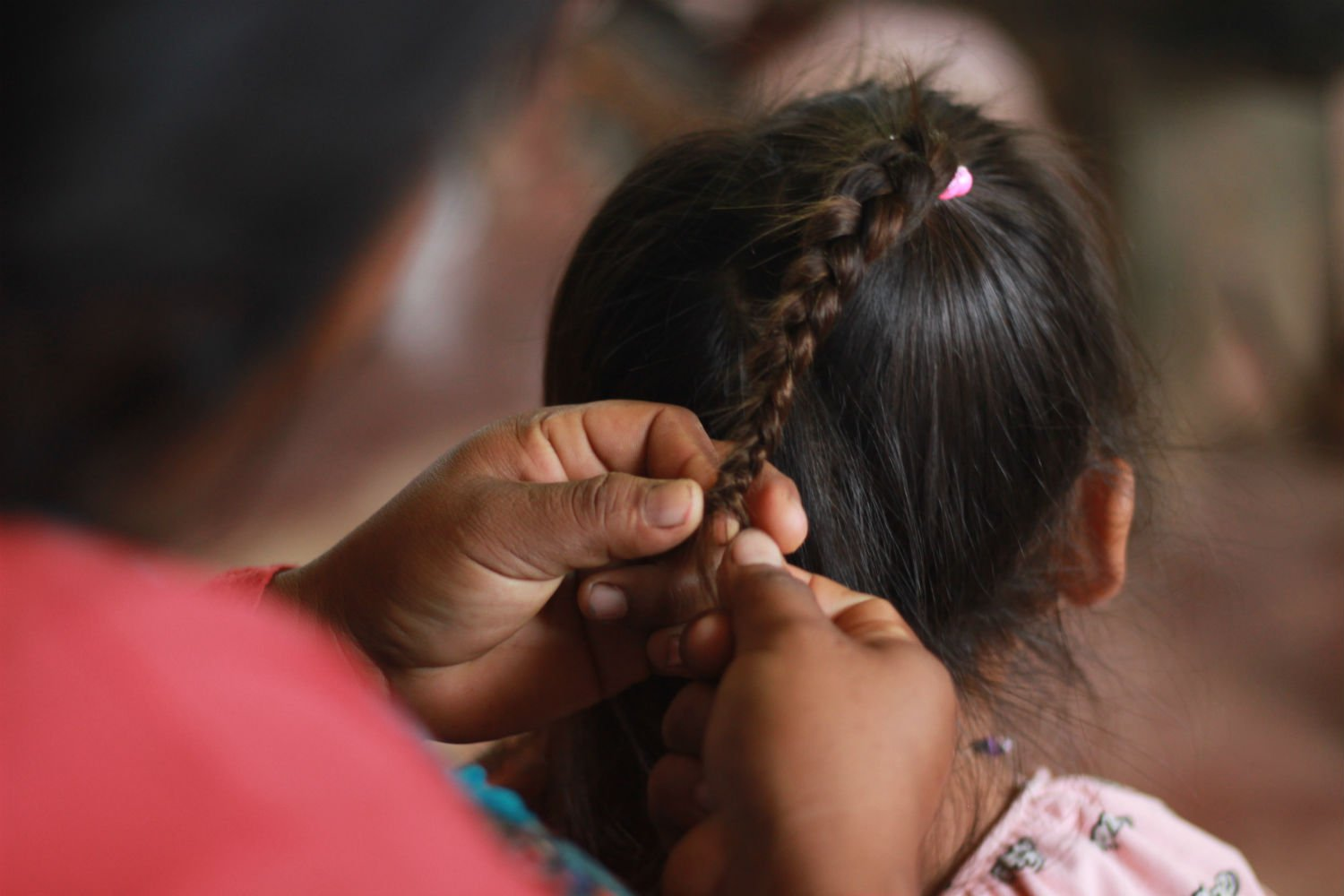 An Achuar mother from the community of Jose Alaya in the Corrientes river basin braids her daughter's hair.