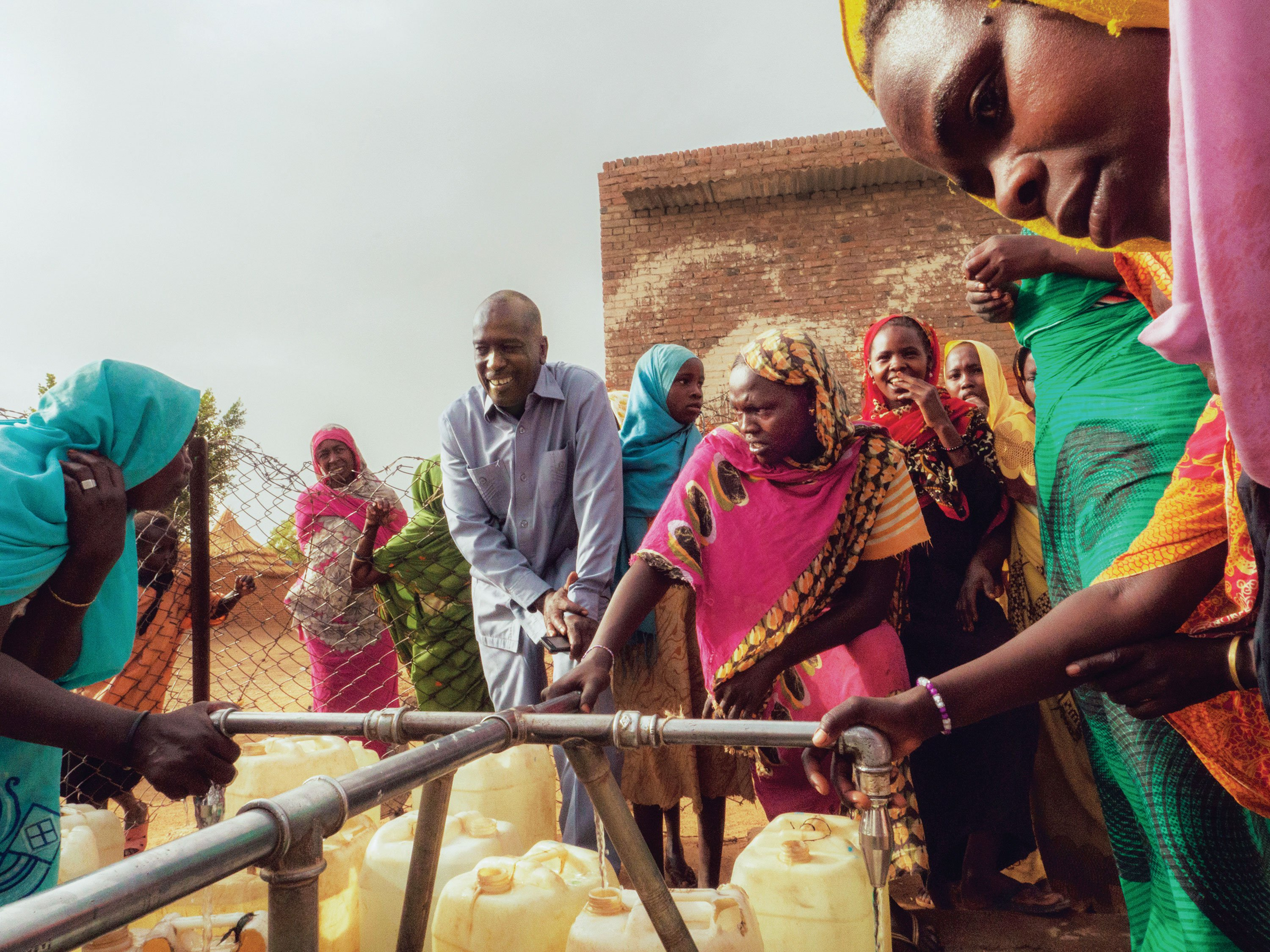 "Mohammed Mohammedian of KSCS chats with women collecting water at a tap stand in Kebkabiya. ""In the past five years, there have been four major crises in the area of Kebkabiya. In each case, we were the first aid agency to arrive with help."""