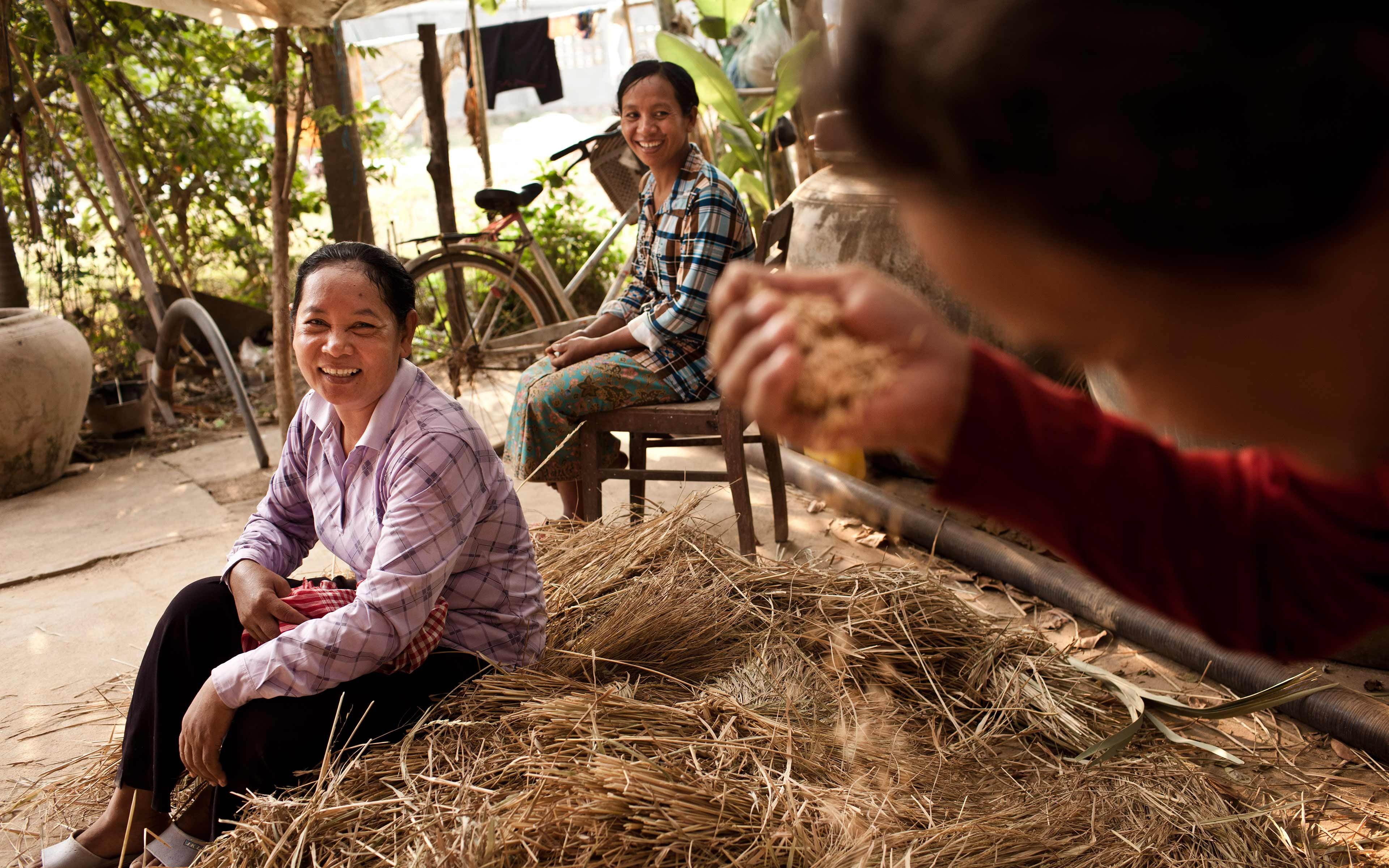 Khek Koeu (left) visits with neighbors at her home in Pursat province. She and six other farmers in her village got specialized training to become rice seed producers, which helps area farmers to access high-quality seed.