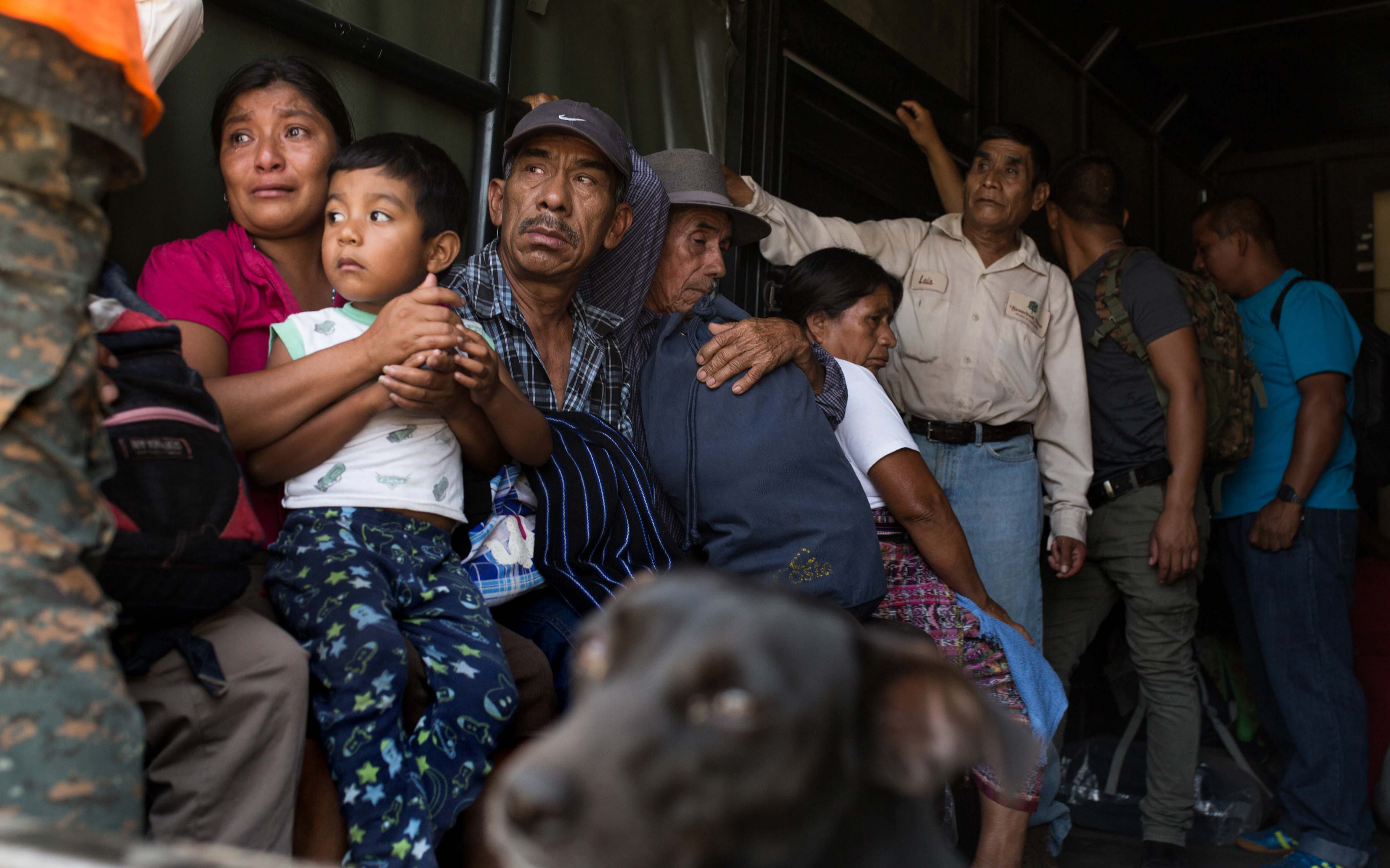 Abi Hernandez holds her 4-year-old son Rodrigo in the back of a Guatemala Army truck as she and her neighbors are evacuated from La Trinidad, on the southern slope of the Fuego Volcano.