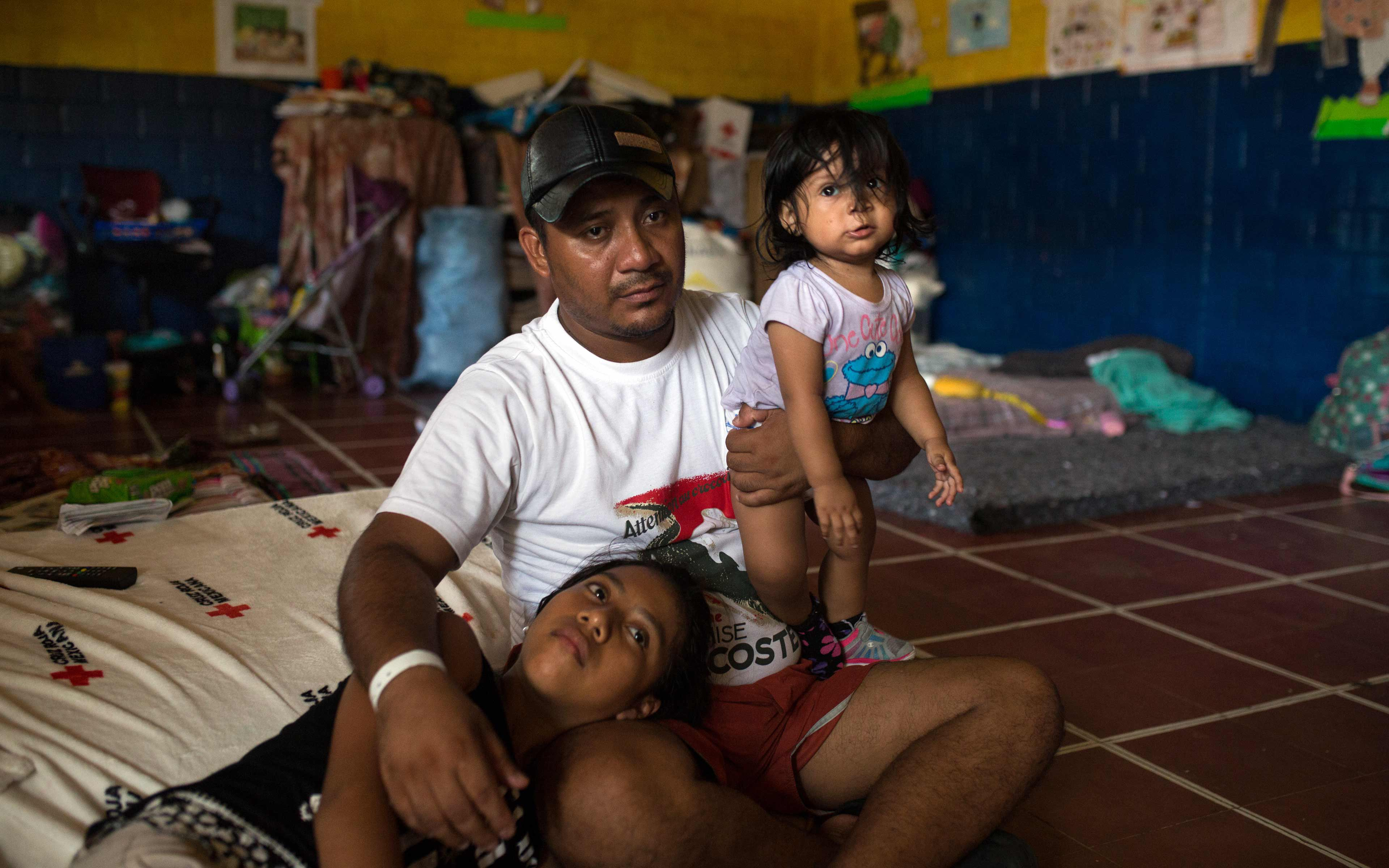 Edwin López and his daughters Melanie (11) and Masiel (1), in the classroom where they are living temporarily.