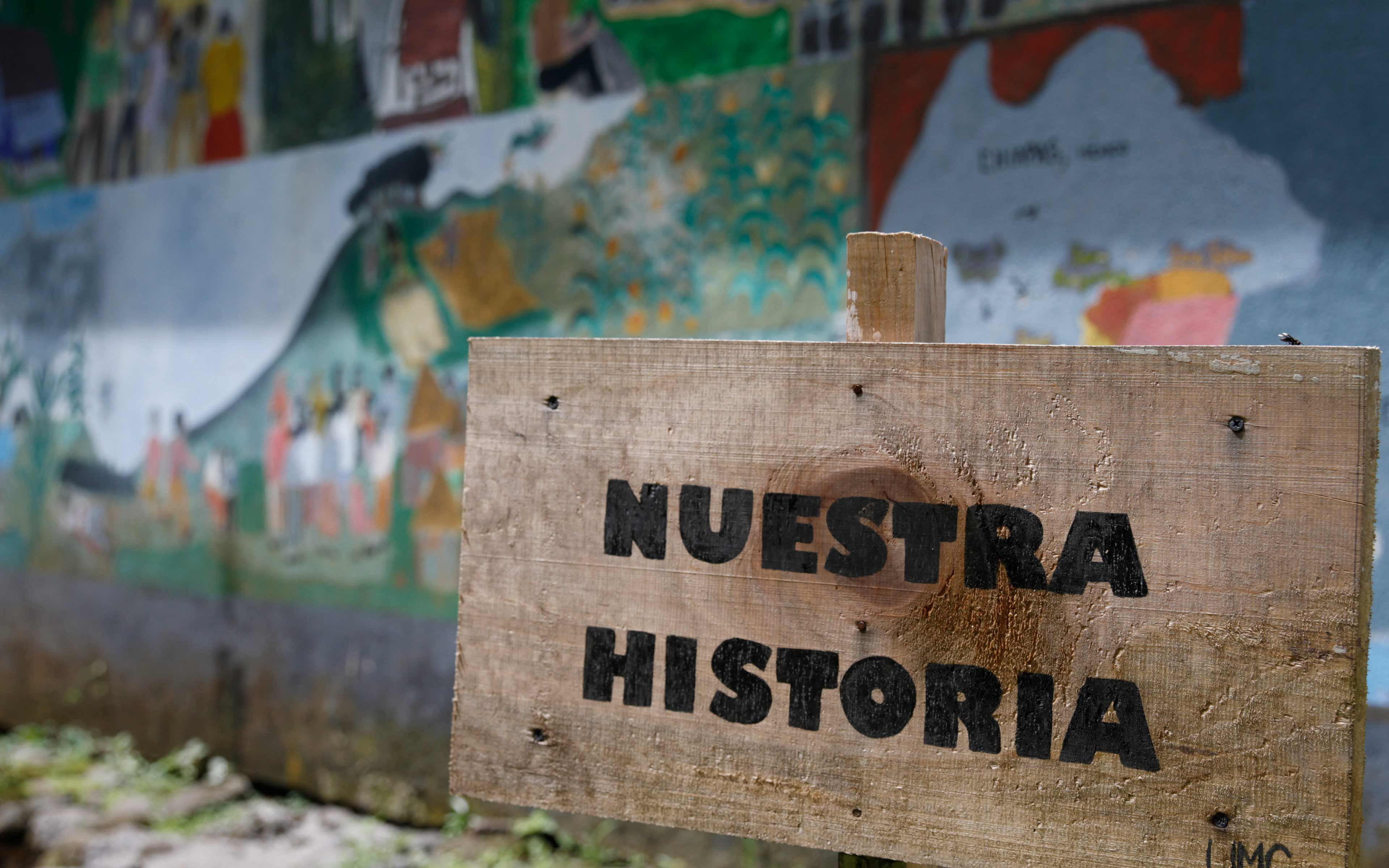 """Our Story:"" A sign in front of mural depicting the tragic history of the community in La Trinidad, from a peaceful indigenous Maya village in the western highlands, to conflict and displacement to Mexico in the 1980s, and finally to repatriation and resettlement in Escuintla after the 1998 Peace Accords."
