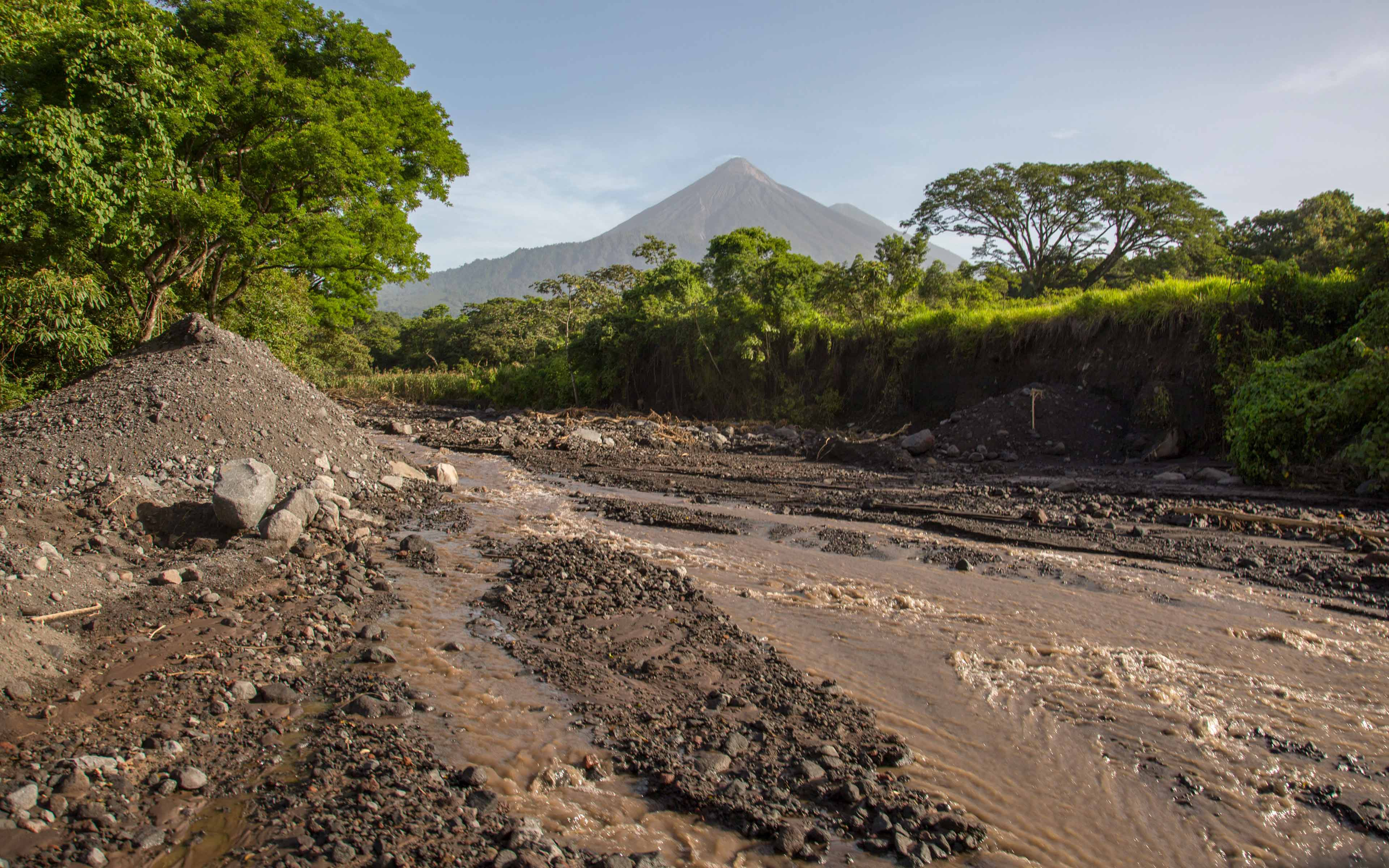 Volcanic ash, rocks, uprooted trees, and other debris has collected in streams and small rivers like this one near the community of La Trinidad on the southern slope. Officials now worry that this unstable material will wash down the mountain and destroy villages if it rains heavily, as it normally does in the summer months.
