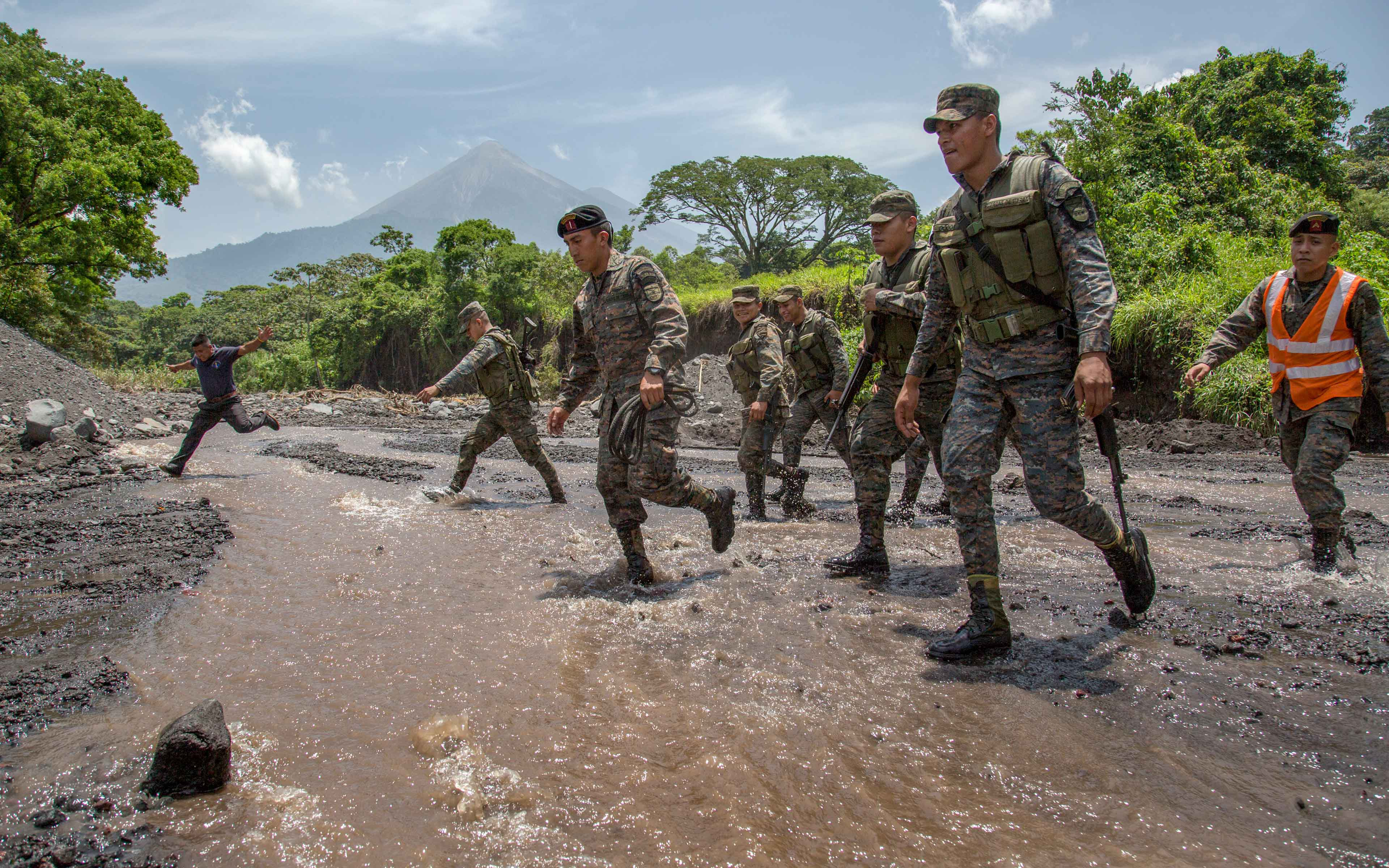 Soldiers walk across a stream amidst volcanic rock and ash and other debris near the community of La Trinidad on the southern slope of Fuego