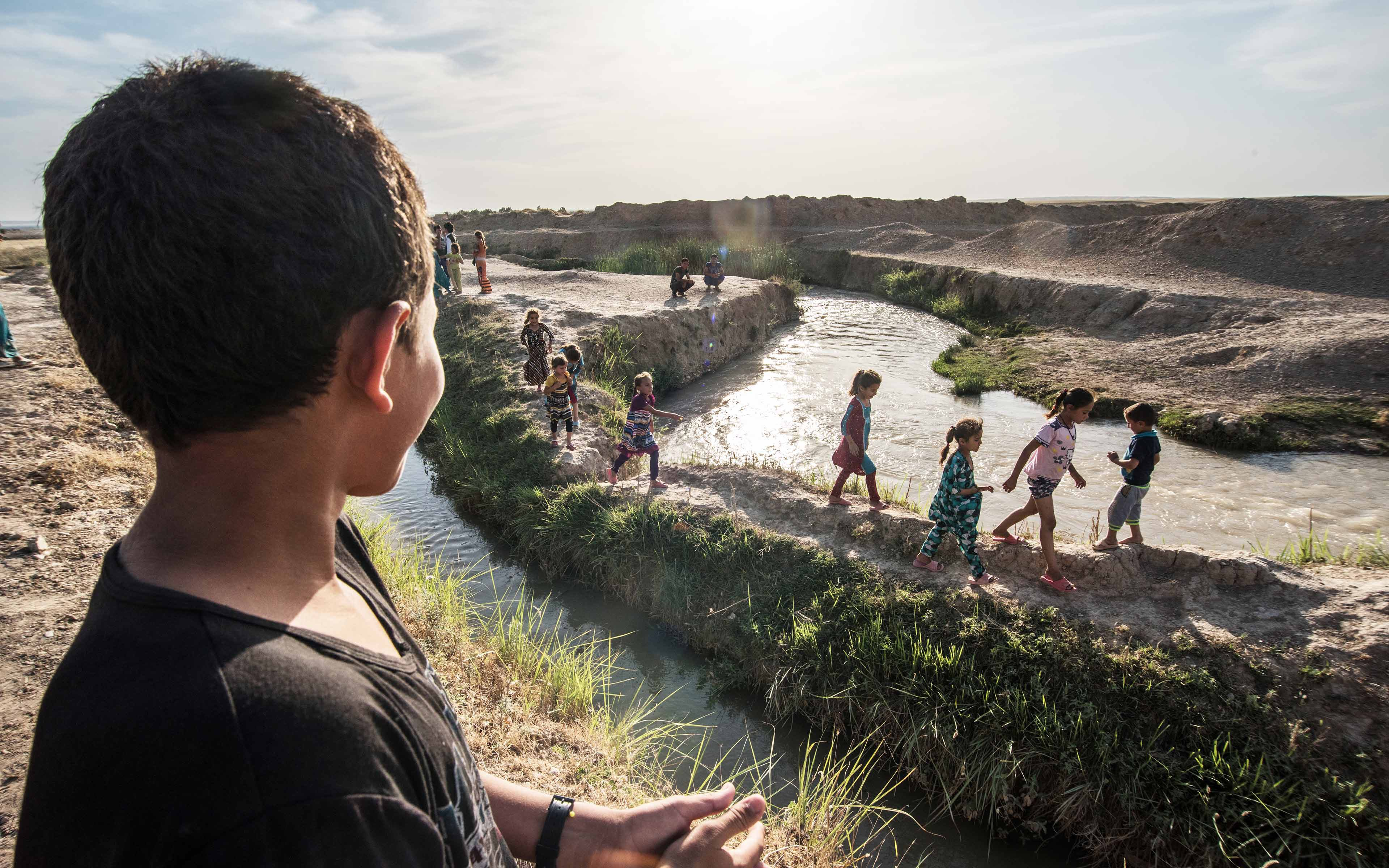 Forced from their homes when ISIS occupied their neighborhoods, these Iraqi children have found a new place to play near an abandoned farm building where some of their families now live.