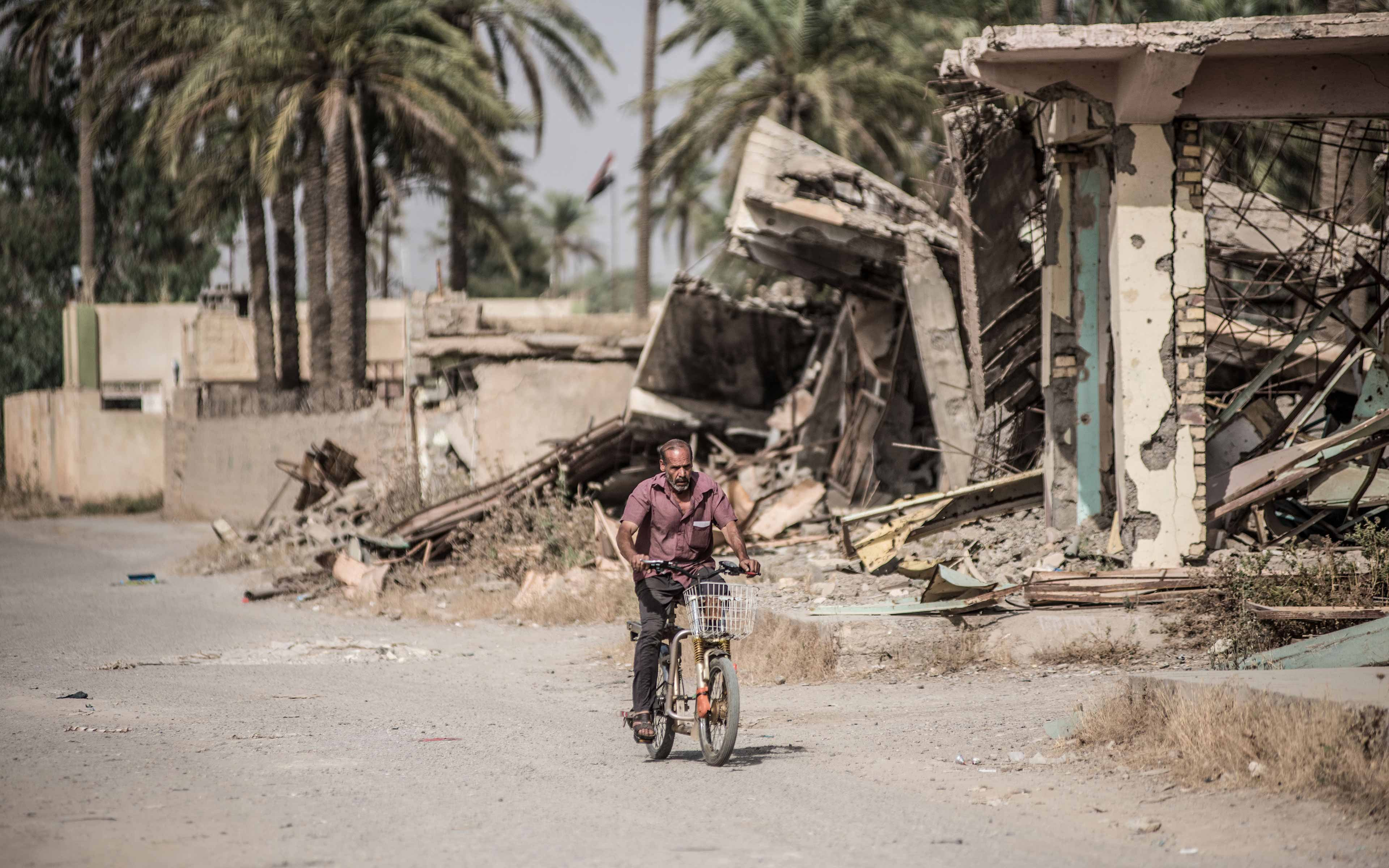 With wreckage around him, a man cycles down the main street of Saadiya. The Iraqi town was largely abandoned after ISIS occupied it in 2014. Though it has now been reclaimed, many residents still have not returned.