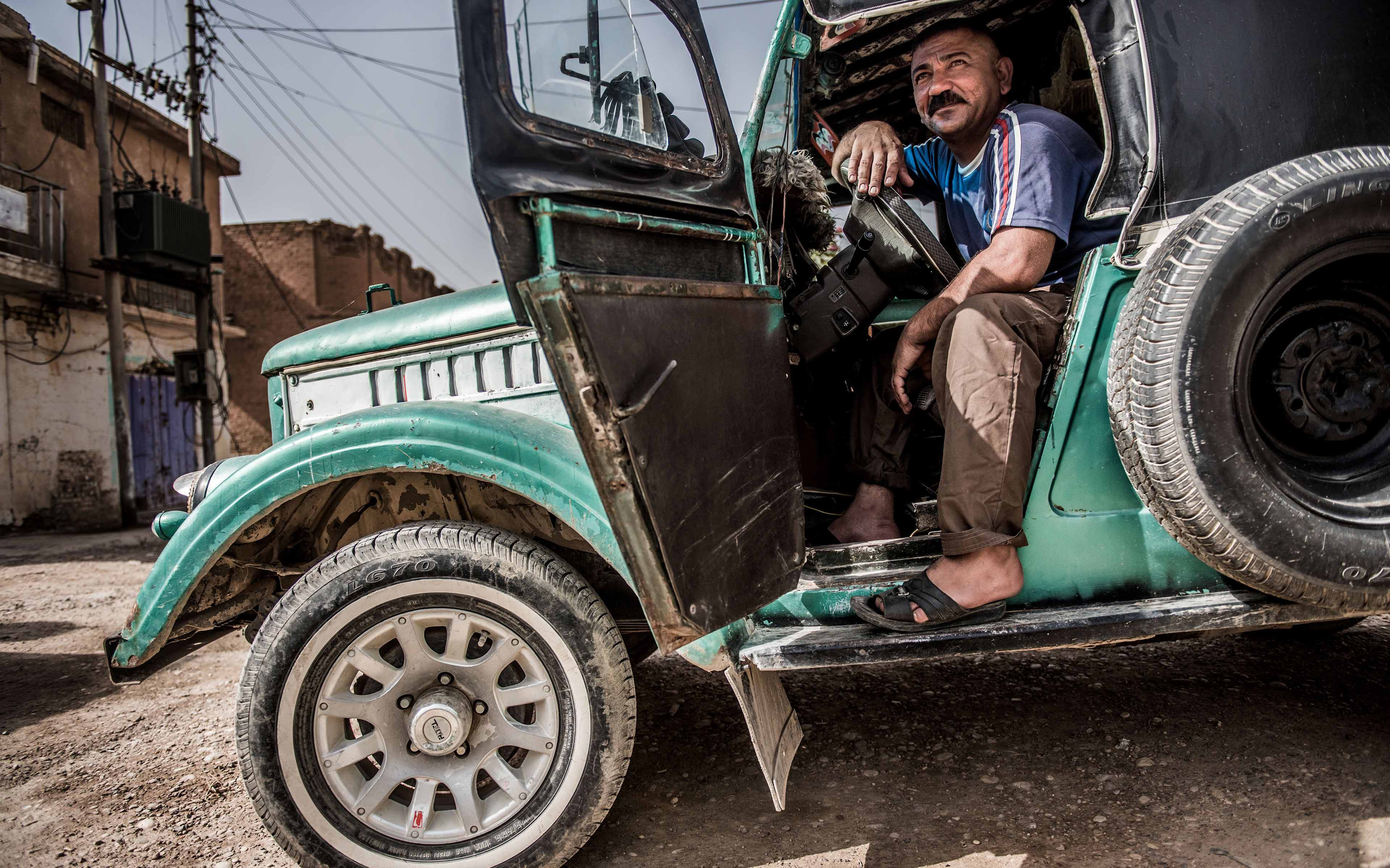Ghasan Ali, whose name has been changed to protect his identity, sits inside his taxi in the Iraqi town of Saadiya. Though ISIS no longer occupies the community, many residents still have not returned and customers needing rides are infrequent.