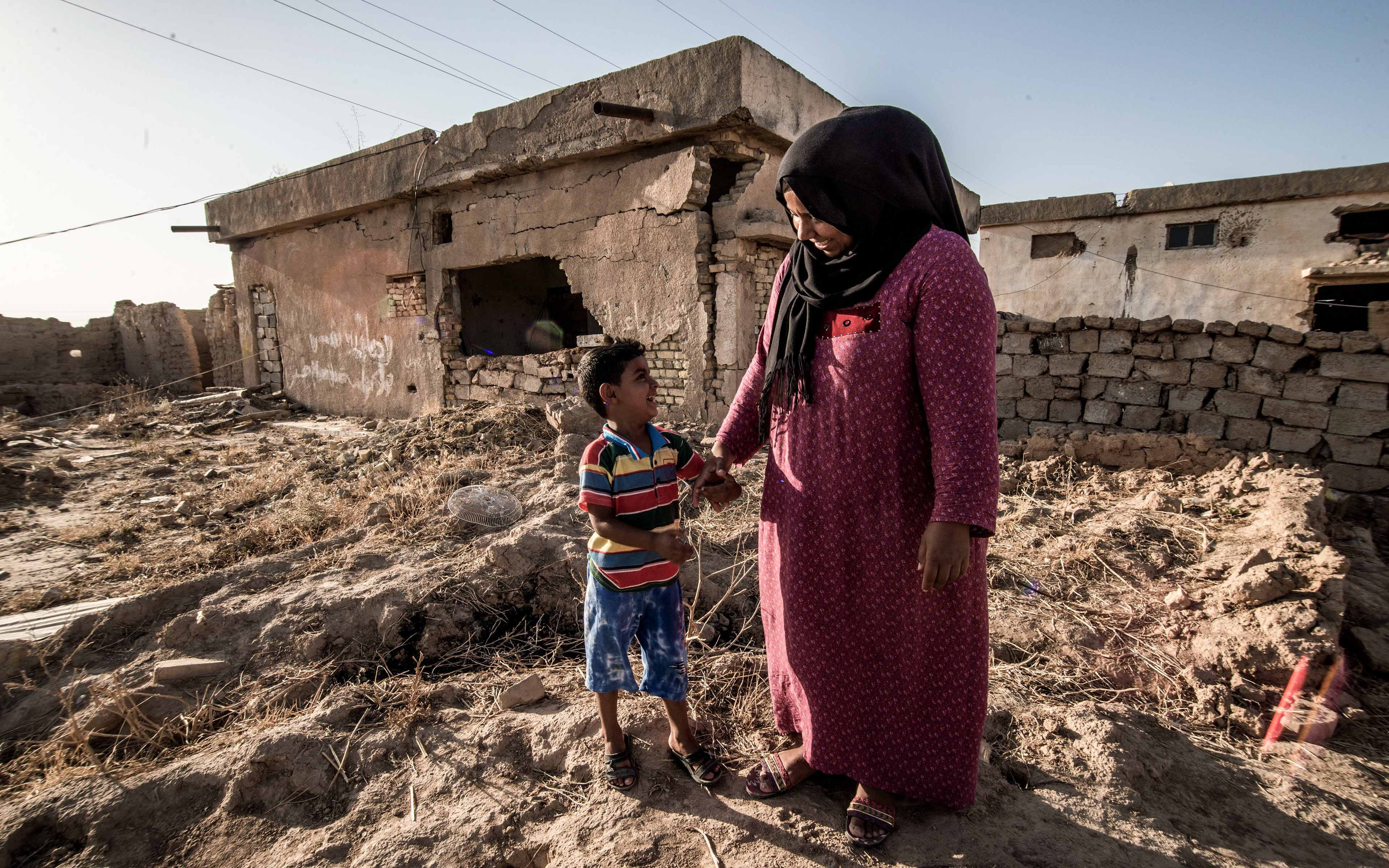 Zahia Hassan, whose name has been changed to protect her identity, talks with her 4-year-old son. The small family has returned to their Iraqi village after it was reclaimed from ISIS.