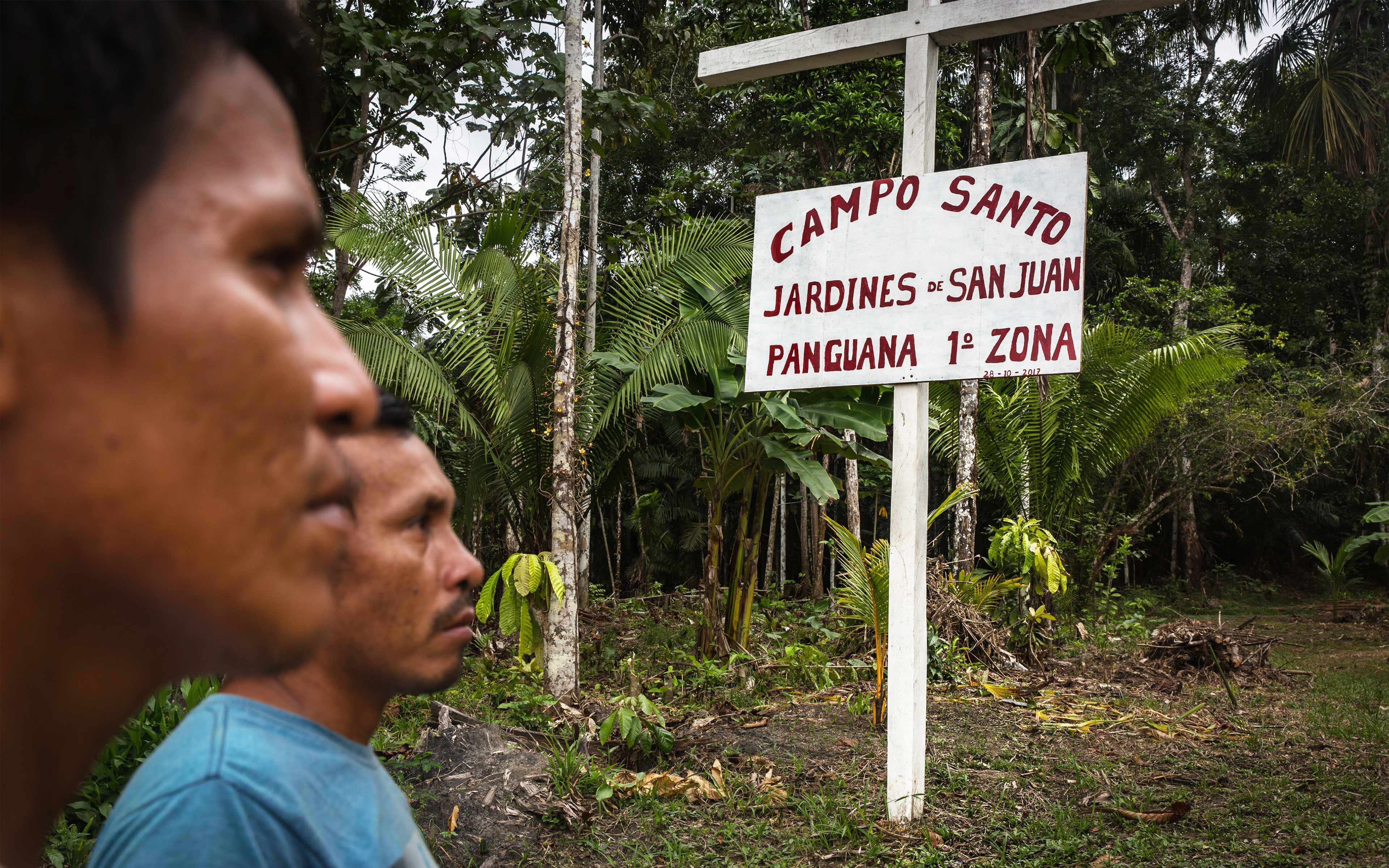 Men from Panguana stand at the entrance to the town's cemetery, on land acquired by Cacao del Peru Norte. Villagers say the company is not asking them to move the cemetery, but it is proposing shifting the entrance to a less convenient location. The Peruvian Society for Environmental Law (SPDA), one of Oxfam's partners in Peru, is helping the community negotiate with the company.