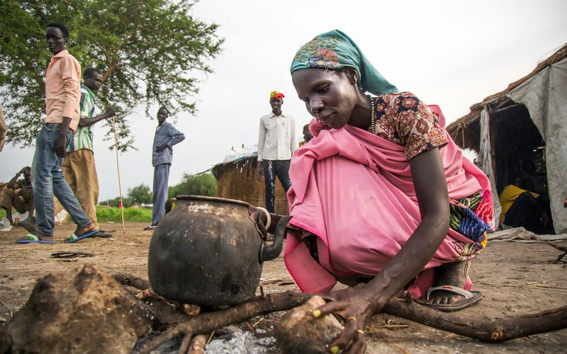 south-sudan-woman-cooking-pot-fire-house-ogb-107643.jpg